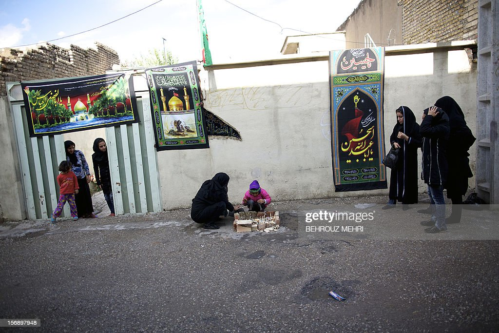 An Iranian women and a child light candles during the 'Chehel Manbar' (Forty Pulpits) ritual a day before Ashura, in the city of Khorramabad, 470 kilometres southwest of Tehran on November 24, 2012. Traditionally, Iranian women of Khorramabad walk barefoot to light candles in 40 designated places in the city centre on the eve of the Ashura, which marks the seventh century slaying of the grandson of Prophet Mohammed, Imam Hussein.