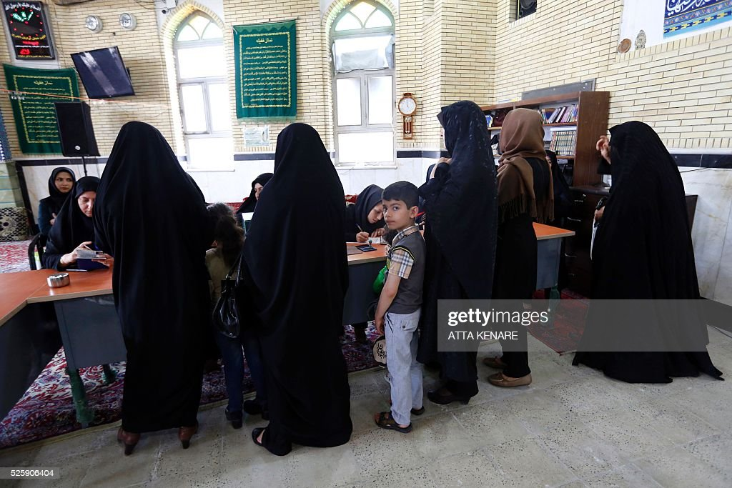 An Iranian young boy looks on as women arrive to cast their vote in the second round of parliamentary elections at a polling station in the town of Robat Karim, some 40 kms southwest of the capital Tehran, on April 29, 2016. Iranians started voting in second round elections for almost a quarter of parliament's seats, the latest political showdown between reformists and conservatives seeking to influence the country's future. Polling stations opened at 8:00 am (0330 GMT) for the ballot which is taking place in 21 provinces, but not Tehran, because no candidate in 68 constituencies managed to win 25 percent of votes cast in initial voting on February 26. Reformists who backed moderate President Hassan Rouhani made big gains in the first round following Iran's implementation of a nuclear deal with world powers, which lifted sanctions blamed for long hobbling the economy. Conservative MPs, including vehement opponents of the West who openly criticised the landmark agreement that reined in Iran's atomic programme, lost dozens of seats and were wiped out in Tehran where reformists won all 30 places in parliament. / AFP / ATTA