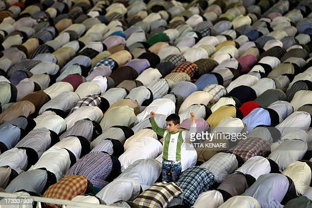 An Iranian young boy stands among Shiite Muslim worshippers attending the weekly Friday prayer during the Muslim fasting month of Ramadan on July 12...