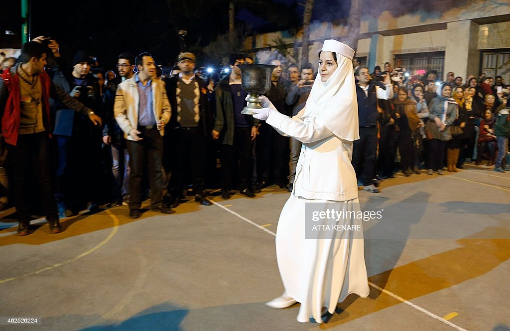 An Iranian Zoroastrian priests carries a vase of coal in order to set firewood ablaze during the annual Zoroastrian Sadeh festival on January 30, 2015 Eeast of Tehran. Sadeh, is an ancient Persian festival that is celebrated by setting a huge bonfire to honour fire and to defeat the forces of darkness, frost, and cold. Sadeh means 'hundred' and refers to one hundred days and nights past the end of summer. KENARE