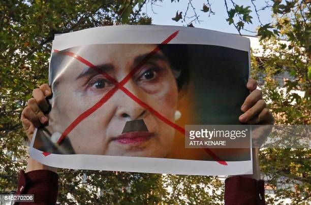 An Iranians deonstrator holds up a defeced poster of Myanmar's State Counselor Aung San Suu Kyi during a protest against violence in Myanmar in front...