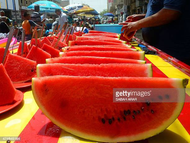 An Iraq vendor sells watermelon slices on a hot day in the capital Baghdad on May 27 2015 AFP PHOTO / SABAH ARAR