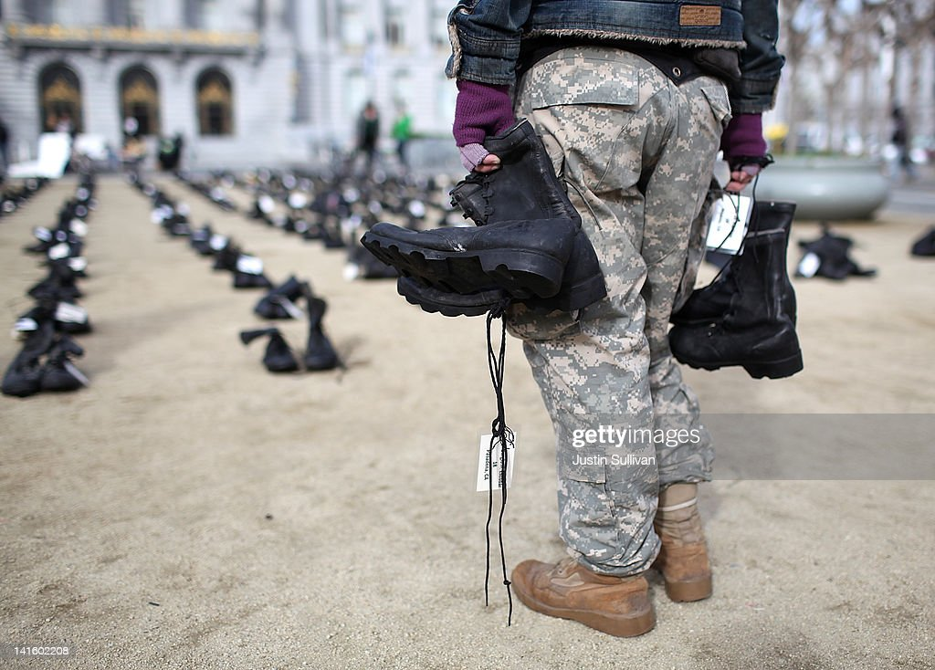 An Iraq war veteran holds pairs of combat boots that are part of the 'Eyes Wide Open' exhibit in front of San Francisco City Hall on March 19, 2012 in San Francisco, California. The Eyes Wide Open exhibition includes a pair of boots for every one of the 481 California servicemen and women who died in the Iraq war.