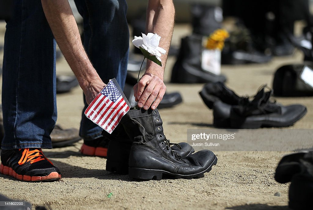 An Iraq war veteran placed an American flag in a pair of combat boots that are part of the 'Eyes Wide Open' exhibit in front of San Francisco City Hall on March 19, 2012 in San Francisco, California. The Eyes Wide Open exhibition includes a pair of boots for every one of the 481 California servicemen and women who died in the Iraq war.