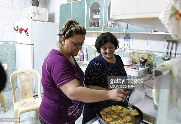 An Iraqi Armenian refugee cooks with her friend on June 18 at her temporary home in the Hasaka region some 650 kms northeast of Damascus near the...
