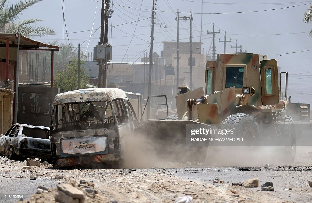 An Iraqi army armoured loader clears debris from a street in Fallujah, 50 kilometres (30 miles) from the capital Baghdad, after forces retook the embattled city from the Islamic State group on June 26, 2016. Iraqi Prime Minister Haider al-Abadi urged all Iraqis to celebrate the recapture of Fallujah by the security forces and vowed the national flag would be raised in Mosul soon. While the battle has been won, Iraq still faces a major humanitarian crisis in its aftermath, with tens of thousands of people who fled the fighting desperately in need of assistance in the searing summer heat. ALI