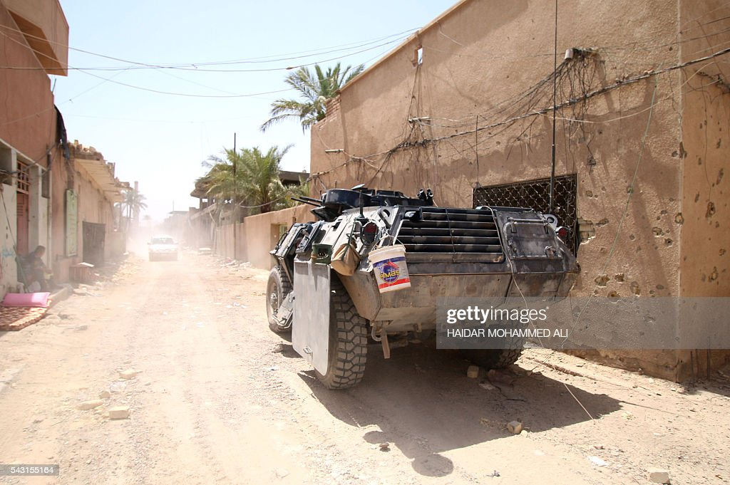 An Iraqi army armoured personnel carrier (APC) drives in a street of Fallujah, 50 kilometres (30 miles) from the capital Baghdad, after forces retook the embattled city from the Islamic State group on June 26, 2016. Iraqi Prime Minister Haider al-Abadi urged all Iraqis to celebrate the recapture of Fallujah by the security forces and vowed the national flag would be raised in Mosul soon. While the battle has been won, Iraq still faces a major humanitarian crisis in its aftermath, with tens of thousands of people who fled the fighting desperately in need of assistance in the searing summer heat. ALI