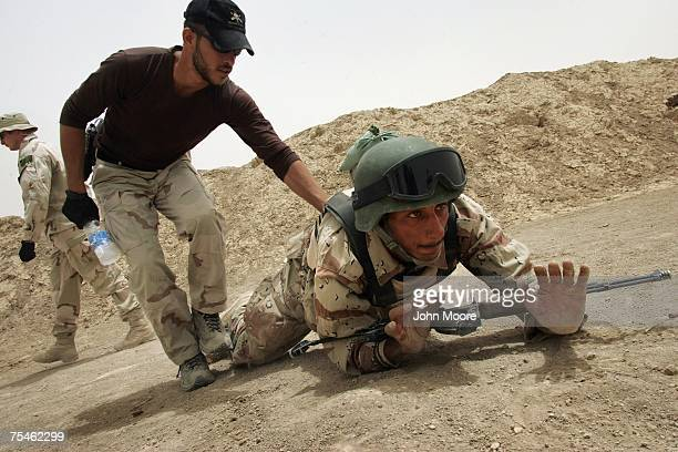 An Iraqi army commando teaches a junior soldier during a combat training course July 18 2007 in Baqouba Iraq Some 60 young recruits are going through...