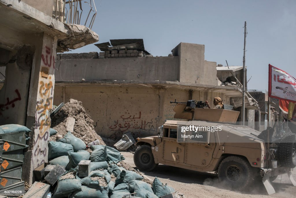 An Iraqi Army humvee flying a Shia flag passes an Iraqi Army position on June 23, 2017 in the frontline neighbourhood of Tal Aptar, which borders the Islamic State occupied Old City of west Mosul. Iraqi forces continue to encounter stiff resistance with improvised explosive devices, car bombs, heavy mortar fire and snipers hampering their advance.