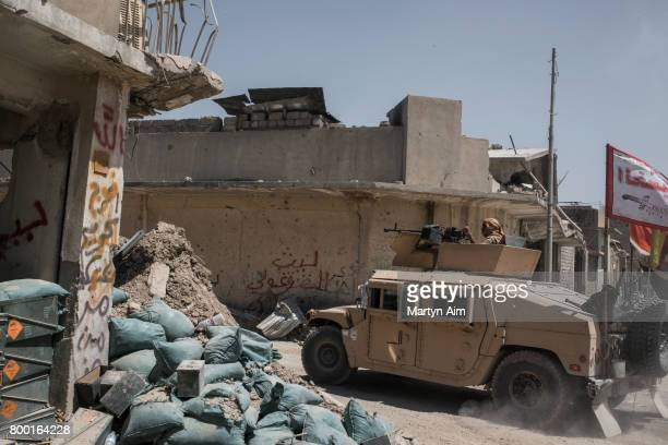 An Iraqi Army humvee flying a Shia flag passes an Iraqi Army position on June 23 2017 in the frontline neighbourhood of Tal Aptar which borders the...