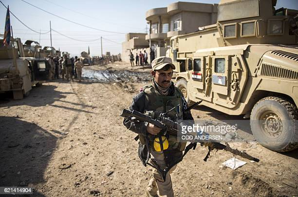 TOPSHOT An Iraqi army sniper from the 9th armoured division walks to take his position in the area of Ali Rash adjacent to the eastern AlIntissar...