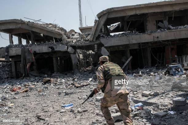 An Iraqi Army soldier runs through Islamic State sniper fire as his division advances June 17 2017 in alShifa the last district of west Mosul under...