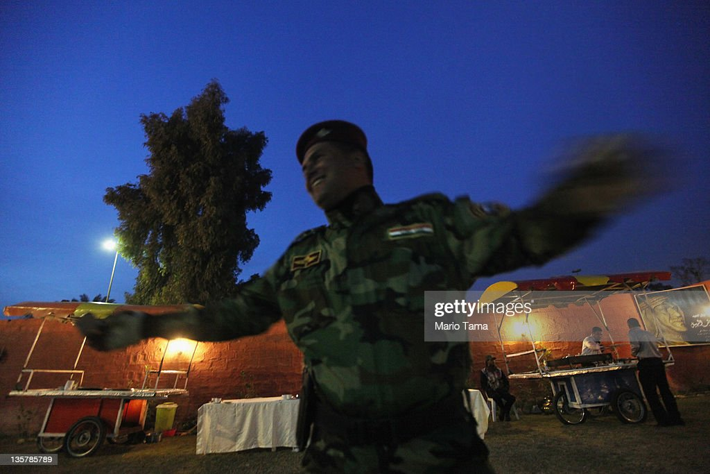 An Iraqi Army special forces soldier laughs at a women's art exhibition sponsored by Iraqi Parliament member Safi Asiheil in a posh Baghdad neighborhood on December 14, 2011 in Baghdad, Iraq. Iraq is transitioning nearly nine years after the 2003 U.S. invasion and subsequent occupation. American forces are now in the midst of the final stage of withdrawal from the war-torn country. At least 4,485 U.S. military personnel have died in service in Iraq. According to the Iraq Body Count, more than 100,000 Iraqi civilians have died from war-related violence.