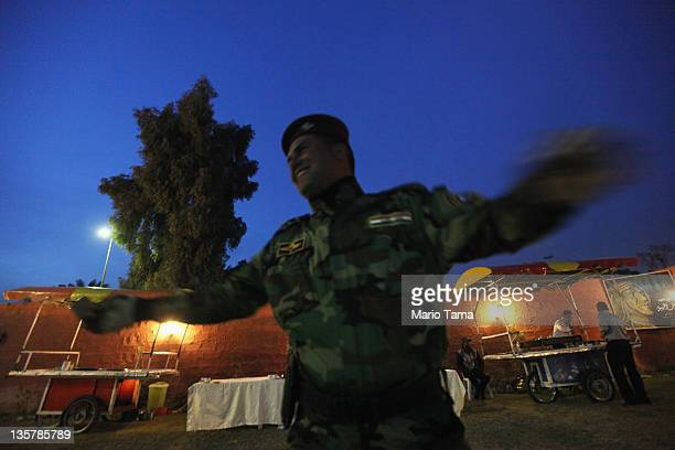 An Iraqi Army special forces soldier laughs at a women's art exhibition sponsored by Iraqi Parliament member Safi Asiheil in a posh Baghdad...