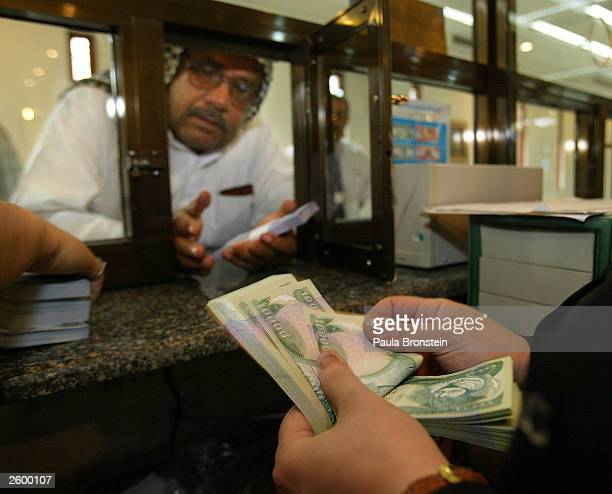 An Iraqi bankteller counts the new Iraqi dinar while dealing with a customer at the Bank of Baghdad October 152003 in Baghdad as the currency is...