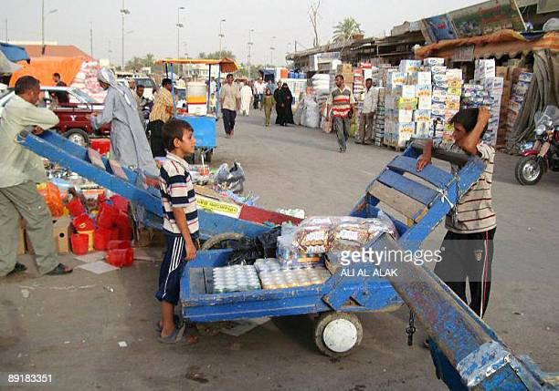 An Iraqi boy chats with his friend as he takes a break from pushing his wooden cart laden with goods through a market in the southern town of Kut...