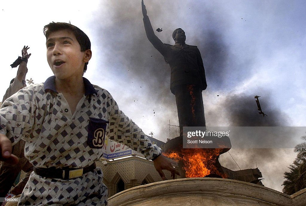 An Iraqi boy cheers as a statue of ousted Iraqi President Saddam Hussein is set ablaze during an impromptu celebration on the streets April 12, 2003 in downtown Baghdad, Iraq. The crowd at first tried to topple the large statue but when they could not, it was set on fire instead while chanting anti-Saddam Hussein slogans.
