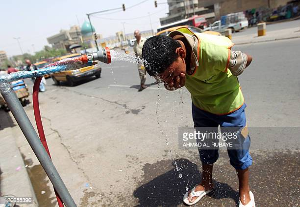 An Iraqi boy cools off under a public shower in central Baghdad amid a heat wave on August 8 2011 AFP PHOTO/AHMAD ALRUBAYE