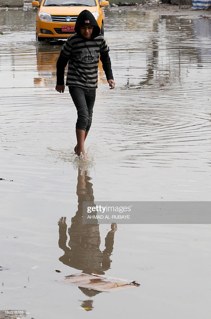 An Iraqi boy crosses a flooded street in Baghdad after heavy rainfall overnight on January 29, 2013. Baghdad suffered from the worst rains to hit the capital in 30 years in December 2012 which left four people dead and many of the Iraqi capital's residents struggling to cope with heavy flooding. AFP PHOTO/AHMAD AL-RUBAYE