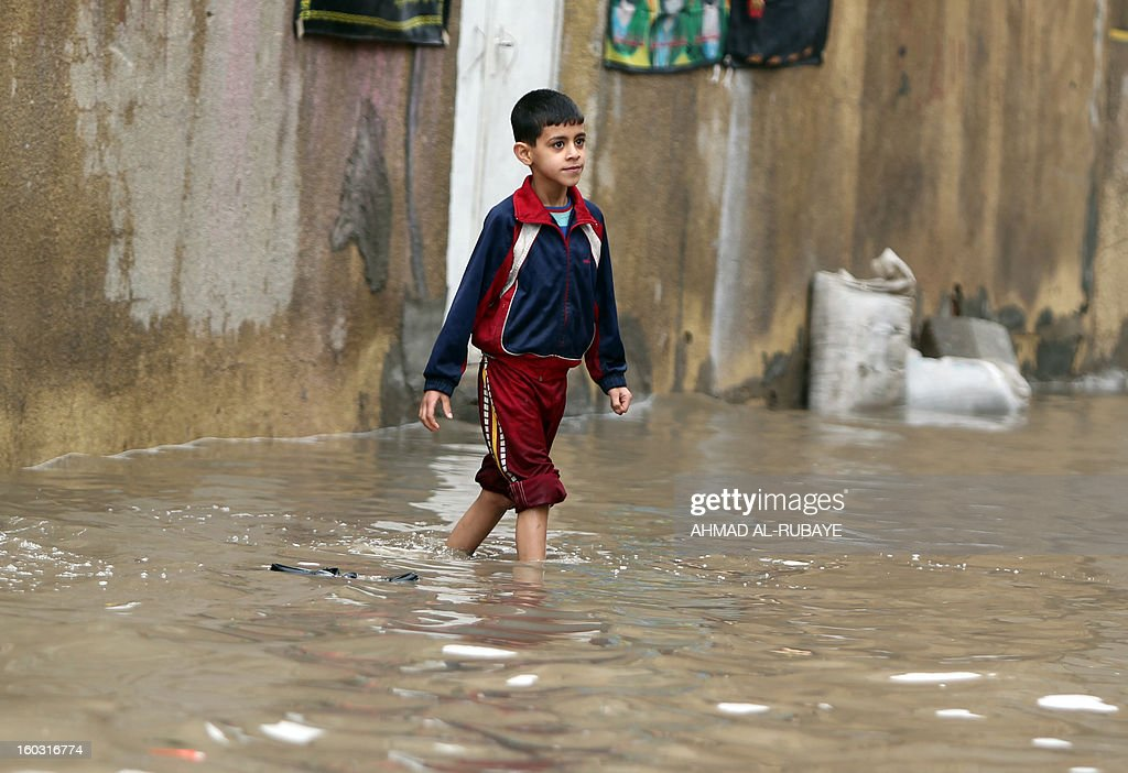 An Iraqi boy crosses a flooded street in Baghdad after heavy rainfall overnight on January 29, 2013. Baghdad suffered from the worst rains to hit the capital in 30 years in December 2012 which left four people dead and many of the Iraqi capital's residents struggling to cope with heavy flooding.