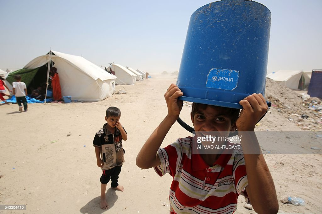 An Iraqi boy displaced from the city of Fallujah carries an empty bucket on his head at a newly opened camp where hundreds of displaced Iraqis are taking shelter in Amriyat al-Fallujah on June 27, 2016, south of Fallujah. Iraqi forces on June 26 wrapped up operations in Fallujah and declared the area free of jihadists from the Islamic State (IS) group after a month-long operation. The government said the destruction caused by the fighting was limited and vowed to do its utmost to allow the tens of thousands of displaced civilians to return to their homes. RUBAYE