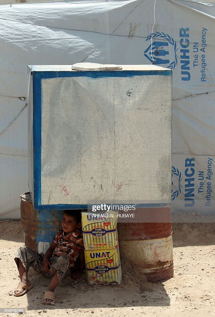 An Iraqi boy displaced from the city of Fallujah sits in the shade at a newly opened camp where hundreds of displaced Iraqis are taking shelter in Amriyat al-Fallujah on June 27, 2016, south of Fallujah. Iraqi forces on June 26 wrapped up operations in Fallujah and declared the area free of jihadists from the Islamic State (IS) group after a month-long operation. The government said the destruction caused by the fighting was limited and vowed to do its utmost to allow the tens of thousands of displaced civilians to return to their homes. RUBAYE