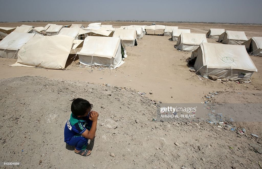 An Iraqi boy displaced from the city of Fallujah squats nearby tents at a newly opened camp where hundreds of displaced Iraqis are taking shelter in Amriyat al-Fallujah on June 27, 2016, south of Fallujah. Iraqi forces on June 26 wrapped up operations in Fallujah and declared the area free of jihadists from the Islamic State (IS) group after a month-long operation. The government said the destruction caused by the fighting was limited and vowed to do its utmost to allow the tens of thousands of displaced civilians to return to their homes. RUBAYE