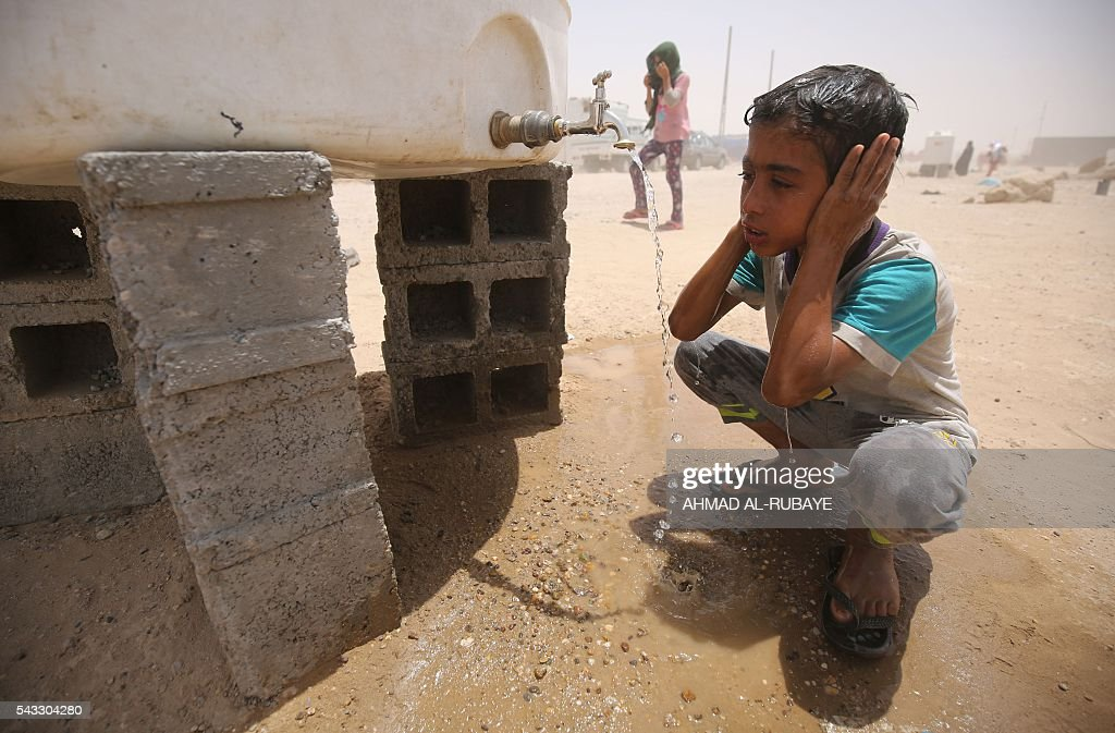 An Iraqi boy displaced from the city of Fallujah washes his face with water at a newly opened camp where hundreds of displaced Iraqis are taking shelter in Amriyat al-Fallujah on June 27, 2016, south of Fallujah. Iraqi forces on June 26 wrapped up operations in Fallujah and declared the area free of jihadists from the Islamic State (IS) group after a month-long operation. The government said the destruction caused by the fighting was limited and vowed to do its utmost to allow the tens of thousands of displaced civilians to return to their homes. RUBAYE