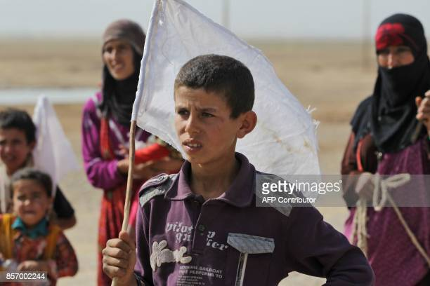 An Iraqi boy displaced from the outskirts of Islamic State group stronghold Hawija raises a white flag while travelling with family members and a...
