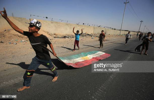 TOPSHOT An Iraqi boy drags a Kurdish flag as Iraqi forces advance towards the centre of Kirkuk during an operation against Kurdish fighters on...