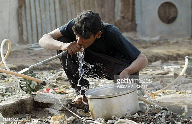An Iraqi boy drinks water from a water pipe crossing an uncovered sewage canal at the area of Fdailiyah southeast of Baghdad 06 December 2007 Many of...