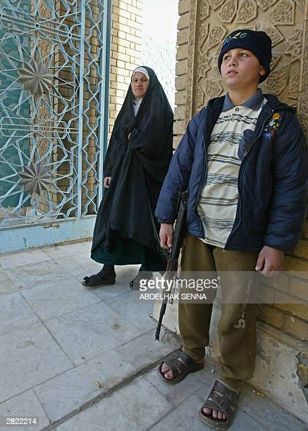 An Iraqi boy holding a gun secures the entrance of the Abu Hanifa Sunni Muslim mosque as an Iraqi woman walks past prior to the Friday midday prayers...