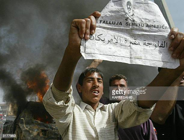 An Iraqi boy holds a leaflet in broken English that reads 'Fallujah the cemetery of the Americans' near a burning car in the flashpoint town of...