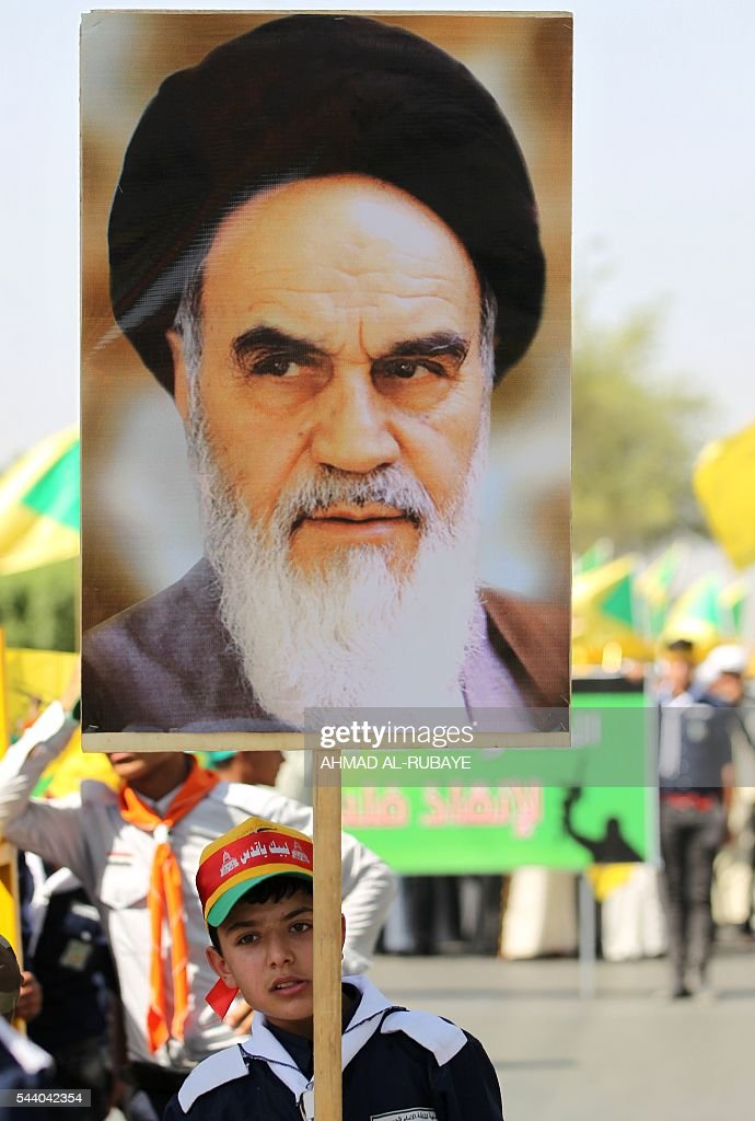 An Iraqi boy holds a poster bearing a portrait of late revolutionary leader Ayatollah Ruhollah Khomeini during a parade marking al-Quds (Jerusalem) Day in the capital Baghdad, on July 1, 2016. RUBAYE