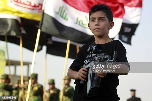 An Iraqi boy holds a weapon during a military parade of fighters from the Iraqi Imam Ali Brigade on August 8 2015 in the mostly Shiite holy city of...
