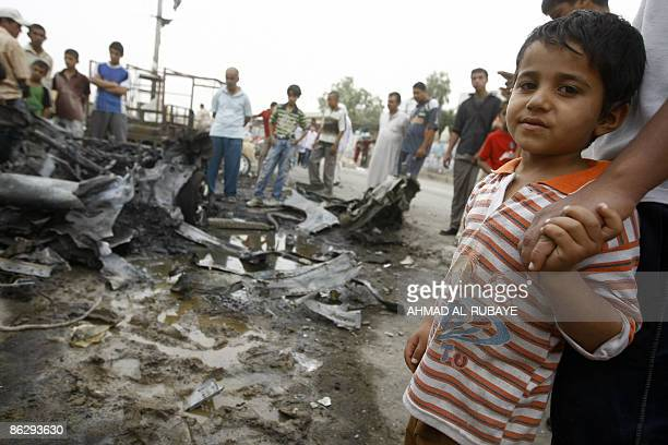 An Iraqi boy holds the hand of his brother as they stand looking at the wreckage following multi explosions last night at a market in Baghdad's...