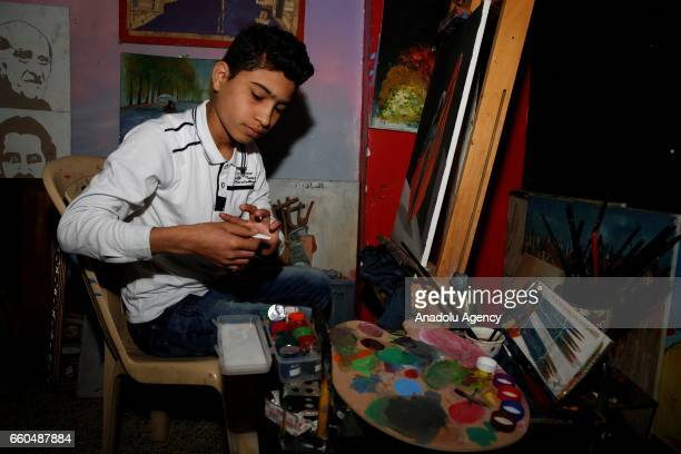 An Iraqi boy paints a paper on a panel in orphanage named 'Safe House for Orphans' in Baghdad Iraq on March 26 2017 An Iraqi benevolent Hesham...