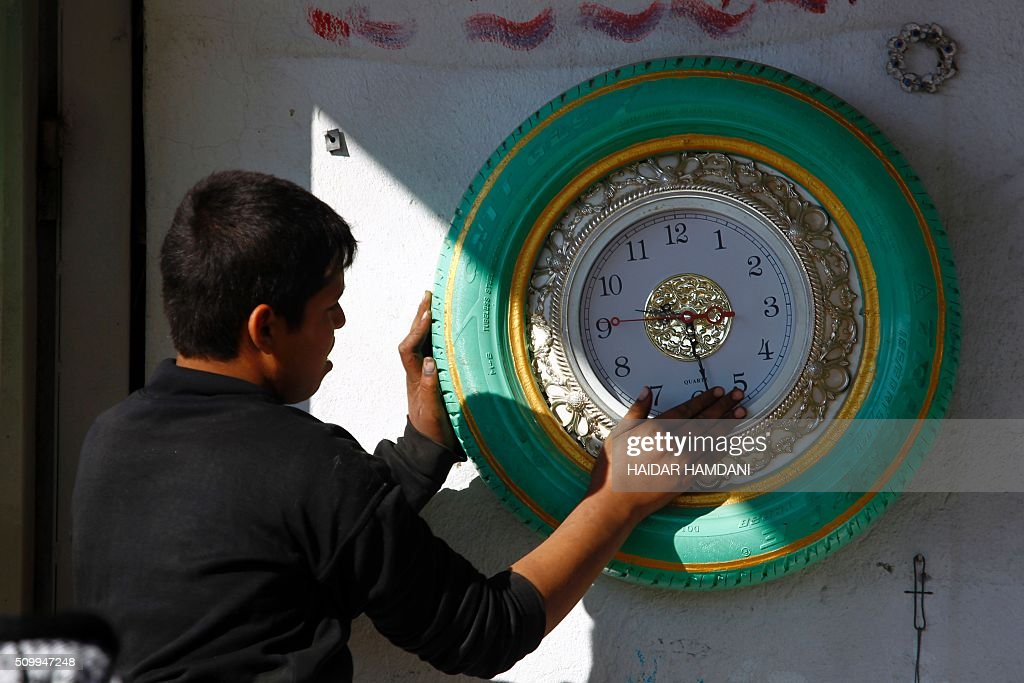 An Iraqi boy places a tire-clock up on the wall at Abu Haidar's tire repair shop, where he transforms unused tires into furniture, in the Diwaniya village, east of the holy Iraqi city of Najaf, on February 13, 2016. / AFP / HAIDAR HAMDANI
