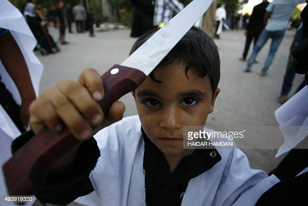 An Iraqi boy poses for a photos holding a knife during a ceremony commemorating Ashura which marks the seventh century slaying of Imam Hussein the...