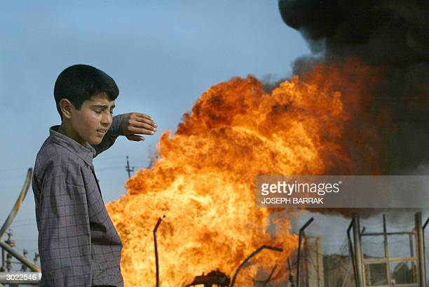 An Iraqi boy protects himself from the heat 28 February 2004 of a burning fuel pipeline 30km west of Samarra which was attacked late 27 February...