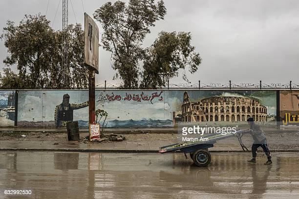 An Iraqi boy pushes a cart past an Islamic State proganada mural painted on a wall in east Mosul Iraq on January 28 2017 The mural featuring an...