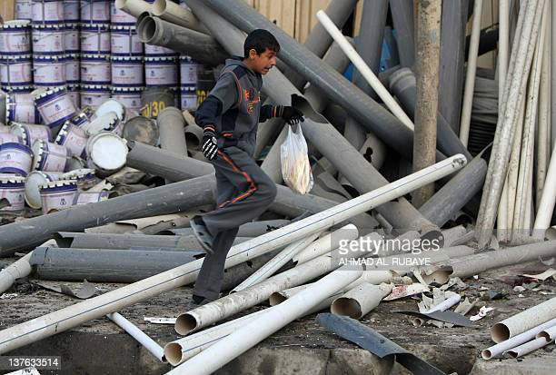 An Iraqi boy reacts as he walks through a damaged area after a bomb ripped through a group of workers in Sadr City in Baghdad on January 24 2012 A...