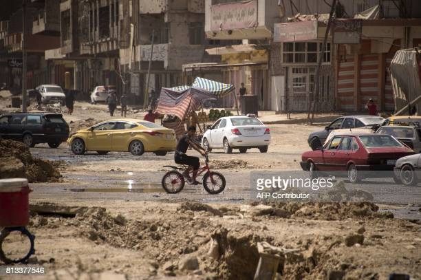 An Iraqi boy rides a bicycle in west Mosul on July 12 2017 after the government declared it had driven the Islamic State group jihadists from their...