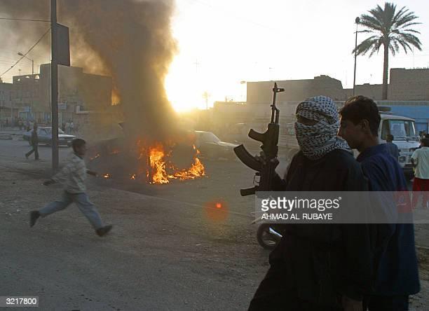 An Iraqi boy runs for cover while Muslim Shiite members of Shiite radical leader Moqtada alSadr Army of Mehdi militia walks pass a burning US Army...