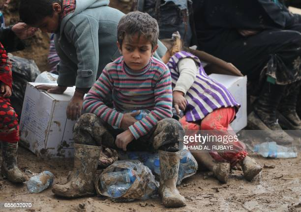 TOPSHOT An Iraqi boy sits as residents from Mosul arrive at the Hamam alAlil camp for displaced people on March 20 during the government forces...