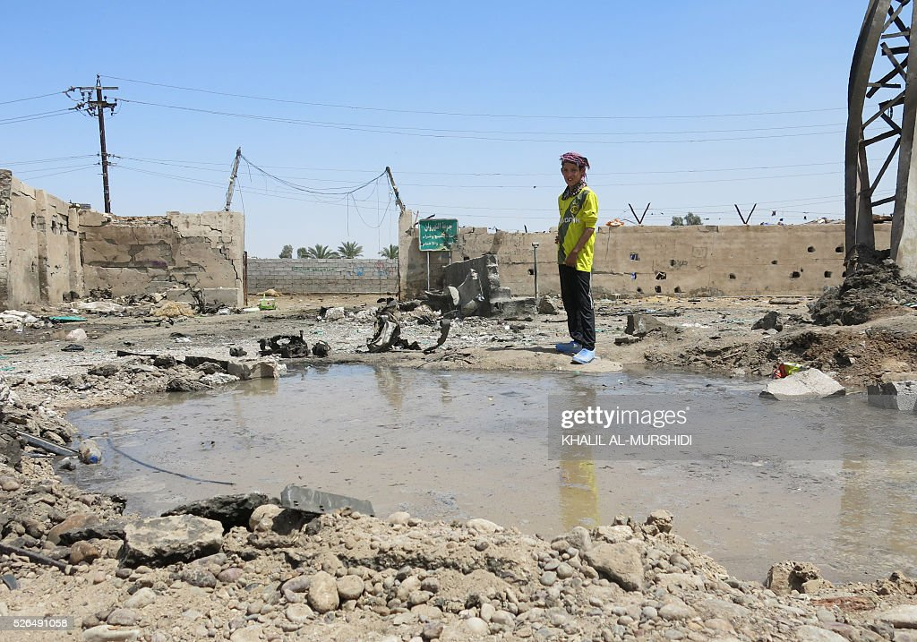 An Iraqi boy stands at the site of a car bomb attack that targeted Shiite pilgrims in Baghdad's Nahrawan area on April 30, 2016. The bomb, which killed at least 14 people, was left on a road in the Nahrawan area used by Shiite pilgrims who are walking to the shrine of Imam Musa Kadhim in northern Baghdad for annual commemorations. / AFP / KHALIL