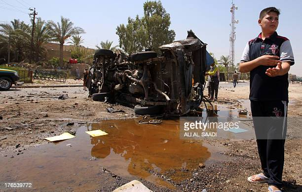 An Iraqi boy stands near a burntout car at the scene of a car bomb attack near the office of AlAhad television channel which is affiliated with a...