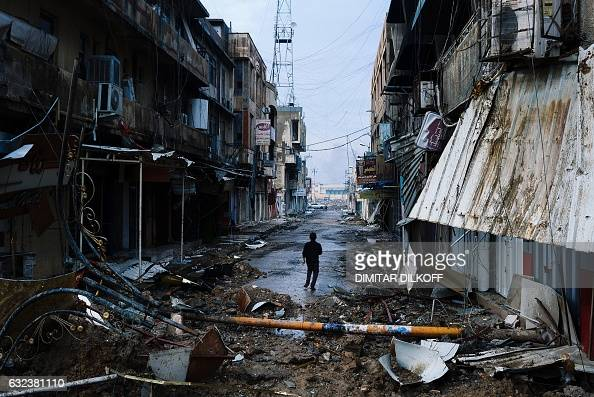 TOPSHOT An Iraqi boy walks down a street near Mosul's University on January 22 a week after Iraqi counterterrorism service retook it from the Islamic...