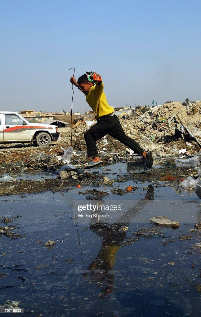 An Iraqi boy walks near sewage water on February 14, 2007 in the street of Baghdad, Iraq.