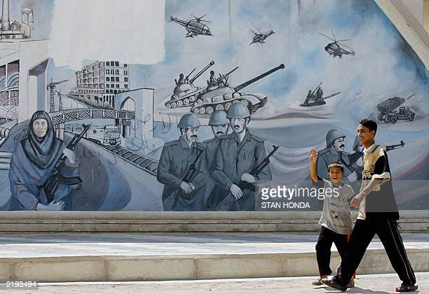 An Iraqi boy waves as he and another boy walk past a mural 17 July 2003 in the center of Ramadi a city about 100kms west of Baghdad US forces are on...